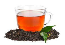 Dry black tea leaves and cup of aromatic beverage on white background royalty free stock photos