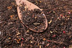 Dry black tea leaves with flower petals and spoon on table royalty free stock photo