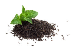 Dry black tea leaves and mint isolated on white.  Royalty Free Stock Photo
