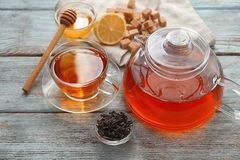 Dry black tea leaves and teapot with cup of aromatic beverage on table royalty free stock photography