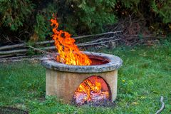 Dry branches burn in isolated campfire pit in the garden. High bright flames flickering on open garden fire pit.  royalty free stock photo