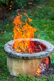 Dry branches burn in isolated campfire pit in the garden. High bright flames flickering on open garden fire pit. Vertical photo stock image