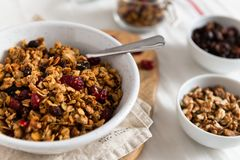Dry breakfast cereals. Crunchy honey granola bowl with flax seeds, cranberries and coconut. Healthy and fiber food. Breakfast time royalty free stock photography