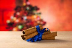 Dry brown cinnamon stick with christmas tree behind stock images