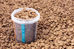 Dry brown pet food (dog or cat) with measure glass Royalty Free Stock Photography