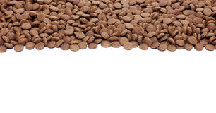 Dry brown pet food (dog or cat) on white background. Dry brown pet food (dog or cat) on the white background Royalty Free Stock Photo