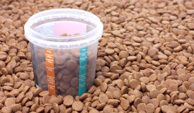 Dry brown pet food with measure glass Stock Images