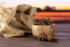 Dry brown star anise fruit autumn field behind. Lot of whole dry brown star anise fruit jute bag with wooden bowl with autumn field and sunset in background royalty free stock image
