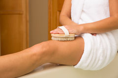 Dry Brushing Top of Thigh. Sitting woman's arm holding dry brush to top of outstretched leg Royalty Free Stock Image