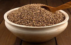 Dry buckwheat in clay bowl  with wooden spoon Stock Photo