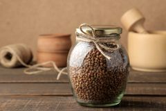 Dry buckwheat groats in a glass jar in the foreground on a wooden brown table. cereals. healthy food. porridge stock images