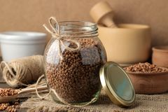 Dry buckwheat groats in a glass jar in the foreground on a wooden brown table. cereals. healthy food. porridge stock photos