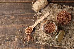 Dry buckwheat groats in a glass jar with a wooden spoon. top view on wooden brown table. cereals. healthy food. porridge stock photography