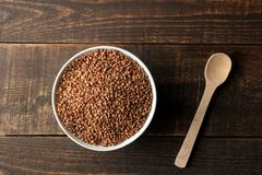 Dry buckwheat groats in a white bowl with a spoon on a wooden brown table. cereals. healthy food. porridge. top view royalty free stock photo