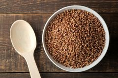 Dry buckwheat groats in a white bowl with a spoon on a wooden brown table. cereals. healthy food. porridge. top view stock image