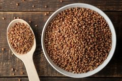 Dry buckwheat groats in a white bowl with a spoon on a wooden brown table. cereals. healthy food. porridge. top view royalty free stock photography