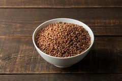 Dry buckwheat groats in a white bowl on a wooden brown table. cereals. healthy food. porridge stock images