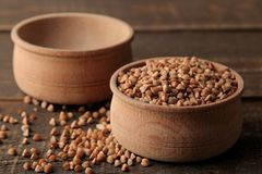Dry buckwheat groats in a wooden bowl on a wooden brown table. cereals. healthy food. porridge stock photos