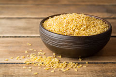 Dry bulgur wheat in ceramic bowl on rustic wooden background Royalty Free Stock Photography