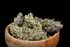 Dry cannabis buds in a bowl. Dry cannabis buds in wooden bowl on black background royalty free stock images