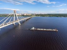 The dry cargo ship barge passes along the Sheksna River after the October cable-stayed bridge. Cherepovets, Vologda region, Russia Royalty Free Stock Photo