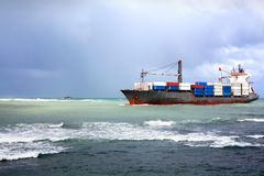 Dry cargo ship, bulk carrier vessel with containers aboard enters the sea harbor in a seaport stock image