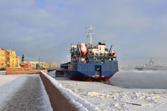 Dry cargo ship on docks in ice, and St. Isaac's Cathedral in frosty haze Royalty Free Stock Photography