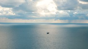 Dry cargo ship in the open sea. Dry cargo ship sails in the open sea. Cloudy rainy weather. The storm is coming. View from afar stock footage