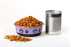 Dry cat dog food in granules in cute bowl and wet canned food. Colorful dry cat dog food in granules in cute bowl isolated on white background. Canned pet food stock photography