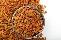Dry cat dog food in granules. Pet treats in metal bowl. Colorful dry cat dog food in granules isolated on white background. Pet treats in metal bowl, view from Stock Photo