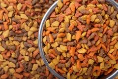 Dry cat dog food in granules. Pet treats in metal bowl. Colorful dry cat dog food in granules. Pet treats in metal bowl, view from top above overhead. Copyspace Stock Photos