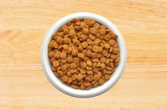 Dry cat food in plate over wooden Royalty Free Stock Image