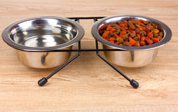 Dry cat food and water in bowls on wooden Stock Photos