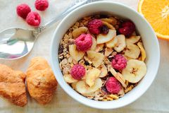 Dry cereals. Bowl with fruits cereals with raspberries and banana royalty free stock photos