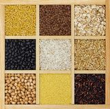 Dry cereals, groats and beans in wooden box top view. Uncooked long white and brown rice, yellow pea, lentil in rustic wood eco container. Staple food royalty free stock photos