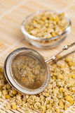 Dry chamomile with tea strainer Stock Photography