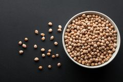 Dry chickpeas in white bowl isolated on dark background Royalty Free Stock Photos