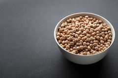 Dry chickpeas in white bowl isolated on dark Stock Photography