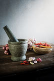 Dry chili pepper and red onion and garlic and stone mortar on an Stock Images