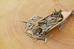 Dry Chinese tea leaves in scoop on chop block royalty free stock photos
