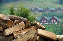 Dry chopped firewood in stalk over cottages at mountain hill stock photo Royalty Free Stock Photo
