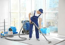 Dry cleaner`s employee removing dirt from carpet. In flat stock images
