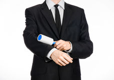 Dry cleaning and business theme: a man in a black suit holding a blue sticky brush for cleaning clothes and furniture from dust is Stock Images
