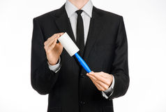 Dry cleaning and business theme: a man in a black suit holding a blue sticky brush for cleaning clothes and furniture from dust is Stock Photography