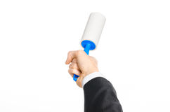 Dry cleaning and business theme: a man in a black suit holding a blue sticky brush for cleaning clothes and furniture from dust is Royalty Free Stock Photos