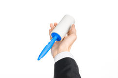 Dry cleaning and business theme: a man in a black suit holding a blue sticky brush for cleaning clothes and furniture from dust is Royalty Free Stock Image
