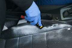 Dry cleaning the car interior, close-up, the hand holding a yellow brush and clean, using the foam, the seat royalty free stock image