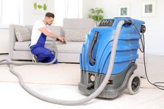 Dry cleaning machine and male worker. On background Royalty Free Stock Photography
