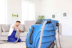 Dry cleaning machine and male worker. On background Stock Photo
