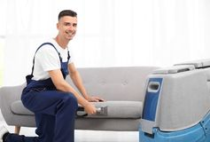 Dry cleaning worker removing dirt from sofa indoors. Dry cleaning male worker removing dirt from sofa indoors Royalty Free Stock Images